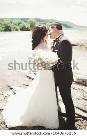 Beautifull wedding couple kissing and embracing near the shore of a mountain river with stones #1040675236
