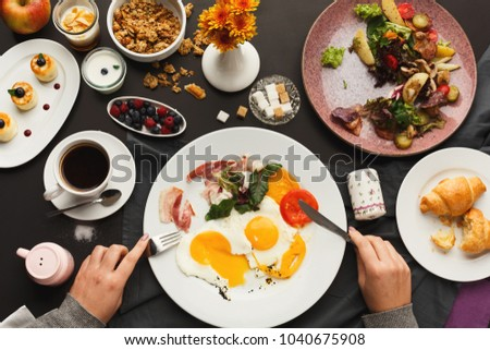 Eating restaurant delicious breakfast with sunny side up fried eggs, bacon, vegetables and greens, croissants and freshly brewed tea served on black table. Nourishing morning meals, top view #1040675908