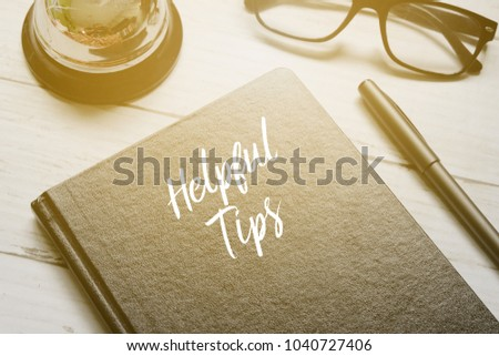 Bell,eyeglasses,pen and notebook written with HELPFUL TIPS on white wooden background with sun flare.