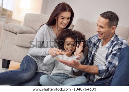 Inspired family. Pretty inspired curly-haired smiling and having fun with her parents while they all sitting on the floor #1040764633