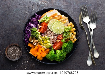 Buddha bowl dish with chicken fillet, brown rice, avocado, pepper, tomato, broccoli, red cabbage, chickpea, fresh lettuce salad, pine nuts and walnuts. Healthy balanced eating. Top view #1040768728