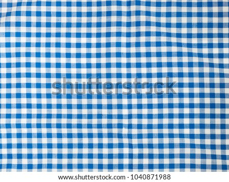 Close up top view of blue and white plaid cotton tablecloth. Background use.