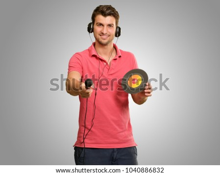 Portrait of man holding mike and disc on grey background #1040886832
