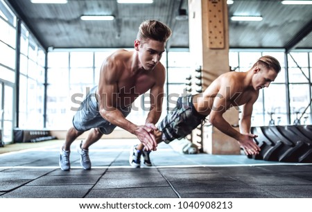 Strong muscular men are working out in gym. Cross fit training. Making push-ups #1040908213