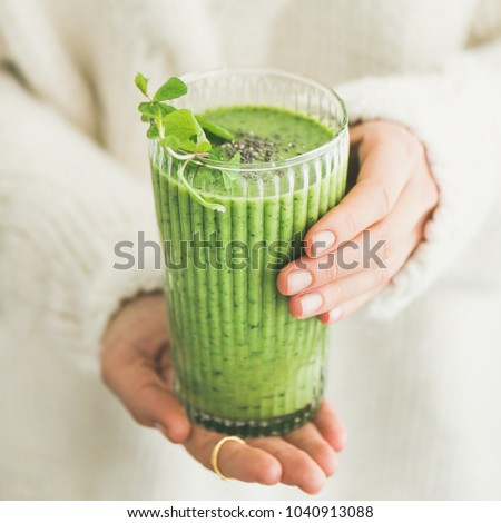 Matcha green vegan smoothie with chia seeds and mint in glass in hands of female wearing white sweater, square crop. Clean eating, alkaline diet, weight loss food concept. #1040913088