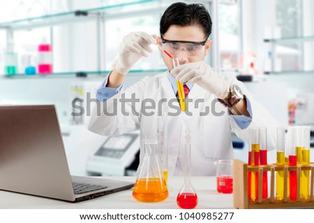 Male scientist doing science research in laboratory #1040985277