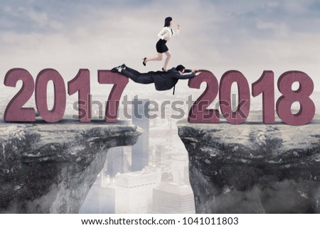 Female entrepreneur running above her partner towards number 2018 in the cliff. Shot with modern city background #1041011803