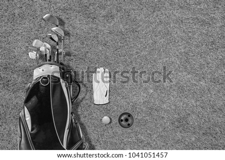 High angle view of golf bag, golf club, gloves and golf ball, with beautiful green lawn floor and golf hole as background.With space to write the text..black &white #1041051457