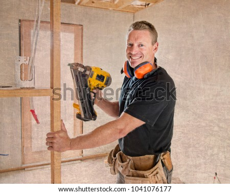 attractive and confident constructor carpenter or builder man working wood with electric drill at industrial construction site in installation and renovation work industry #1041076177