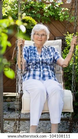 Senior woman  swinging on a garden-swing in summer #104108111