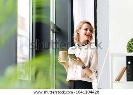 Image of cheerful young business woman in office looking aside chatting by mobile phone drinking coffee. #1041104428