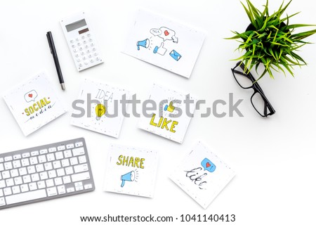 Digital marketing. Work desk of marketing specialist with social media icons and symbols on white background top view copy space #1041140413