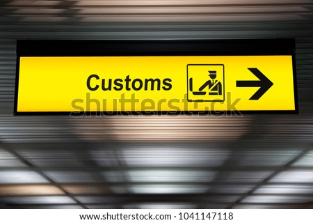 airport customs declare sign with icon and arrow hanging from airport ceiling at international terminal. customs declare for import and export concept