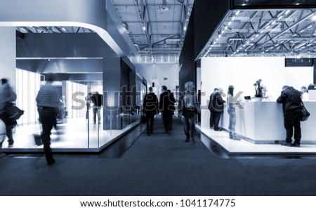 blurred people at a trade fair hall Royalty-Free Stock Photo #1041174775