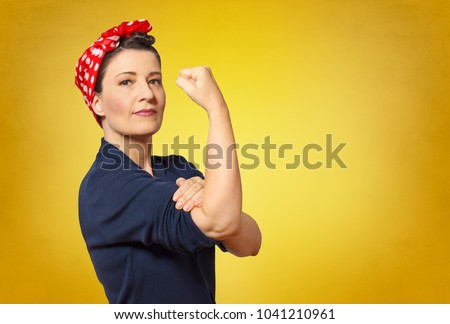 Self-confident middle aged woman with a clenched fist rolling up her sleeve, text space, tribute to american icon Rosie Riveter #1041210961