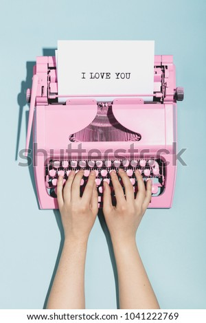 """Woman's hands writing """"I love you"""" on an oldschool pink typewriter. Valentine's day."""