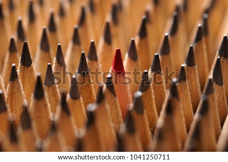 Close up of bunch of identical sharp black graphite pencils and one different, unique red pencil that stands out. Shallow depth of field. Studio shot. Concept of diversity. Concept of uniqueness.