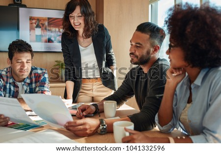 Group of young business people and designer looking at color palette. Team brainstorming in meeting room with color swatches. #1041332596