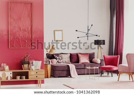 Wooden cupboard against red wall in decorative living room interior with copper table and violet sofa #1041362098