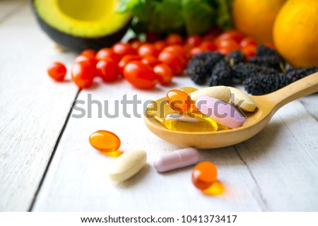Pills and capsules in wooden spoon with fresh fruits.Multivitamins and supplement from fruits concept. #1041373417