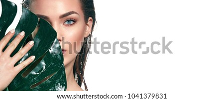 A beautiful young girl in the studio on a white background with wet skin and wet hair holds a large green tropical leaf in hands and covers a part of her face.Fashion, beauty, make-up, cosmetics. #1041379831