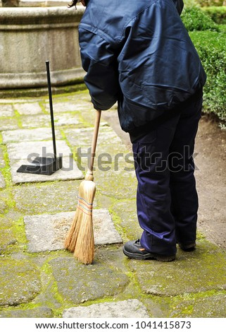 Sweeper, municipal cleaning worker sweeping autumn leaves in the garden #1041415873
