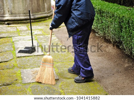 Sweeper, municipal cleaning worker sweeping autumn leaves in the garden #1041415882