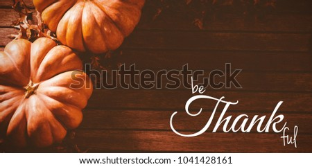 Digital image of happy thanksgiving day text greeting against orange pumpkins with autumn leaves on table