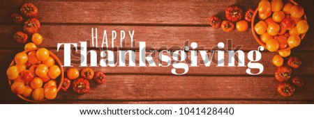 Digitally generated image of happy thanksgiving text against candies with small pumpkins on wooden table