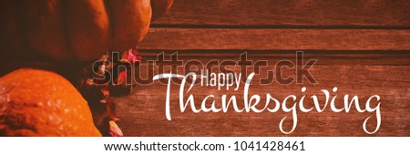 Illustration of happy thanksgiving day text greeting against pumpkins and petals on wooden table