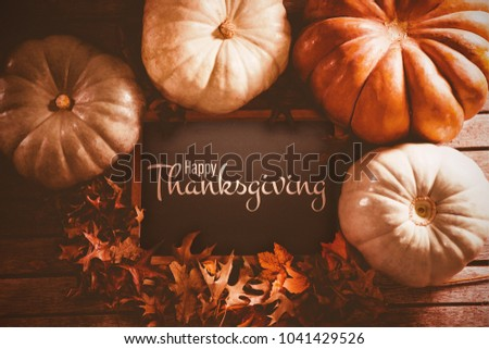 Illustration of happy thanksgiving day text greeting against diverse pumpkin surround black screen and leaf