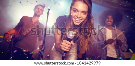 Flying colors against portrait of singer with musicians on stage at nightclub Royalty-Free Stock Photo #1041429979