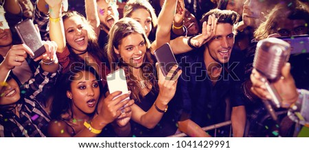 Flying colors against cheerful fans photographing performer at concert #1041429991