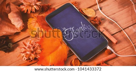 Digital image of happy thanksgiving day text greeting against mobile phone on wood table surround of leaf