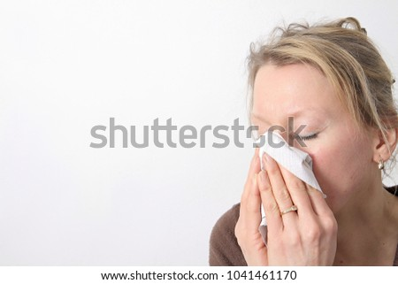 woman with a cold blowing nosein the garden stock image and stock photo #1041461170