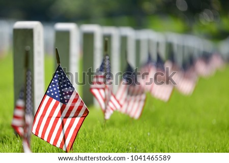 United States National flags and headstones in National cemetery - Circa Washington DC USA Royalty-Free Stock Photo #1041465589