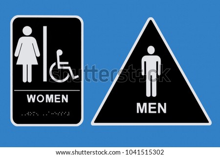 Men's and women's bathroom signs with white images on a black background. Woman's sign is rectangular. Men's is a triangle. Both outlined in white and on a cornflower blue background.