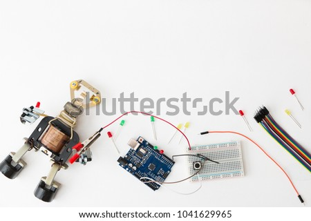 A metal robot and an electronic board that can be programmed. Robotics and electronics. Laboratory in the school. Mathematics, engineering, science, technology, computer code. STEM education for kid.  #1041629965