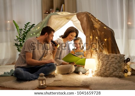 family, hygge and people concept - happy mother, father and little daughter reading book with torch light in kids tent at night at home #1041659728