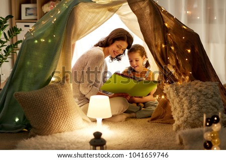 family, hygge and people concept - happy mother and little daughter reading book in kids tent at night at home #1041659746