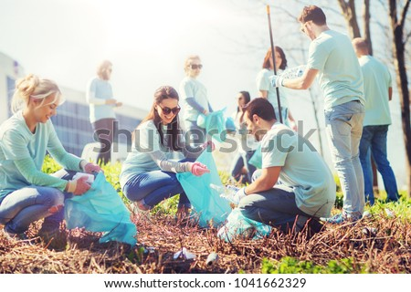 volunteering, charity, cleaning, people and ecology concept - group of happy volunteers with garbage bags cleaning area in park #1041662329