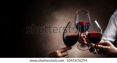 toasting with wine glasses Royalty-Free Stock Photo #1041676294