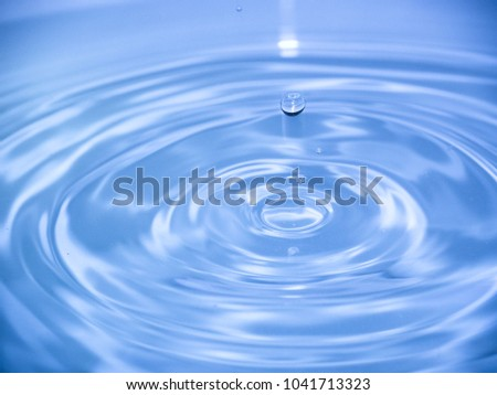 Close up blue water drop falling into water making a reflection concentric circles. Blue wave. #1041713323