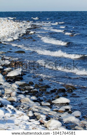 Waves hit the rocky shore of the Jurmo Island in Archipelago national park in Finland covering the stones with ice. #1041764581