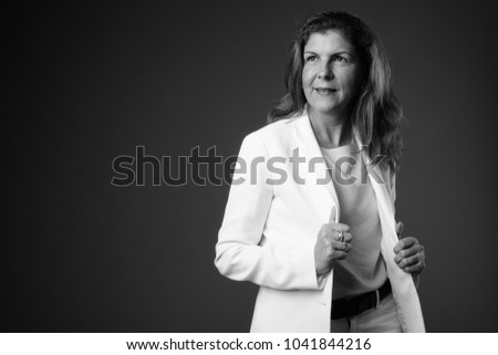 Studio shot of mature beautiful businesswoman against gray background in black and white
