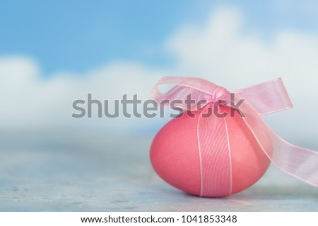 pink painted easter egg with a ribbon against a blurry blue sky with white clouds, copy space, selective focus, narrow depth of field #1041853348