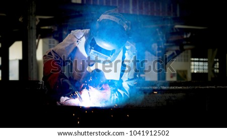 Welding with sparks by Process fluxed cored arc welding , Welding by Welder Thailand , Welder welding steel structure.Industrial steel welder part in factory. #1041912502