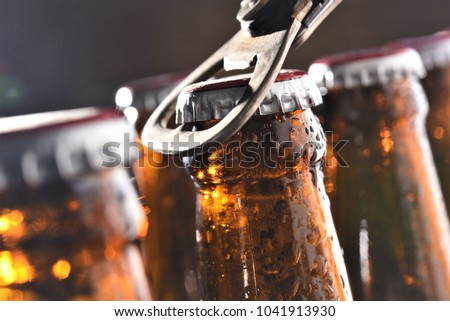 beer bottle opening closeup  Royalty-Free Stock Photo #1041913930