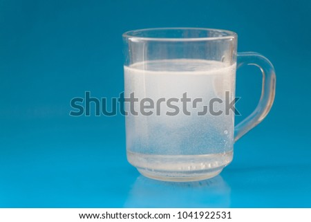 Glass of water and pills on blue background. Selective focus. #1041922531