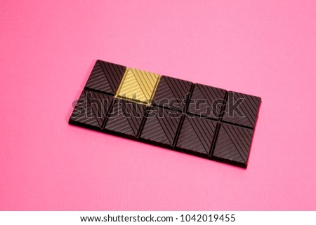 a whole dark chocolate bar with a gold square isolated on a vibrant background. Metaphor of luck. Minimal color still life photography.